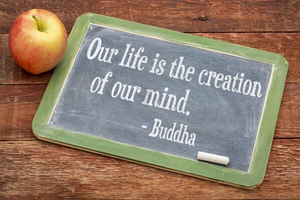 Our life is creation of our mind - Buddha quote  on a slate blackboard against red barn wood